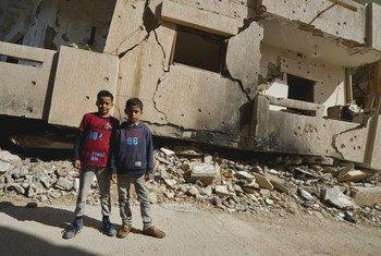 De jeunes garçons se tiennent devant un bâtiment détruit à Benghazi, en Libye (photo d'archives).