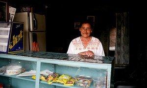 Una mujer en su casa y tienda en Buga, Colombia, donde trabaja por temporadas para la alianza de productores de maracuyá.