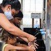 Una mujer y sus niños se lavan las manos en una instalación puesta por UNICEF en Boa Vista, Brasil.