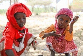 两名埃塞俄比亚女孩正在吃饭,她们是世界粮食计划署学校供餐计划的受益者。