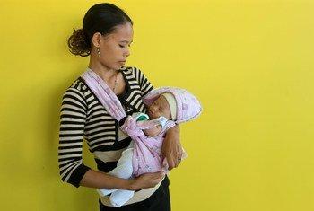 तिमोर लैस्ते को सुआई क्षेत्र में, एक महिला अपने नवजात शिशु के साथ.