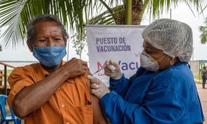 A member of the indigenous community in Colombia receives a COVID-19 vaccination