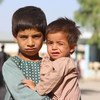 A five-year-old boy holds his younger brother in a displaced persons camp in Kandahar, southern Afghanistan.