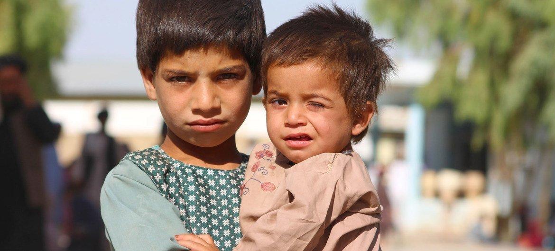 Um menino de cinco anos cuida de seu irmão mais novo em um campo de deslocados em Kandahar, sul do Afeganistão