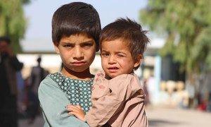 在阿富汗南部坎大哈的一个流离失所者营地,一名五岁男孩抱着他的弟弟。