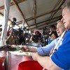 Глава ООН Антониу Гутерриш и руководитель ВПП Дэвид Бисли раздают еду беженцам в Уганде.