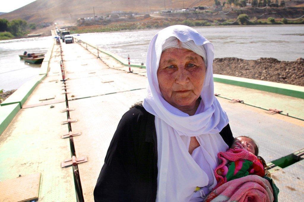 سيدة إيزيدية كبيرة في السن تحمل طفلا عمره 13 يوما تفر من سنجار وتعاود الدخول إلى العراق عبر سوريا (2020).