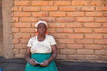 Ruth Sandrum mjane mwenye umri wa miaka 71 akiwa ameshikilia kadi yake ya kumwezesha kupata mgao wa dola 7 kwa ajili ya kununua mahitaji muhimu ya familia yake.