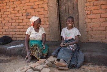 Ruth Sandrum akimsimulia mjukuu wake Yotamu Stanford mwenye umri wa miaka 14 nje ya nyumba yao huko Kasale, wilaya ya Ntcheu nchini Malawi.