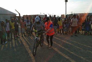 मालाकल में भारतीय और अन्य शान्तिरक्षक लड़कियों को साइकिल सिखाते हुए