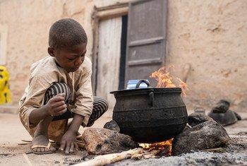 Un enfant aide sa màre à préparer le petit déjeuner au Niger
