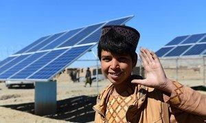 صبي يلوح بيده أمام أمام ألواح الطاقة الشمسية التي توفر الكهرباء لمحطة لضخ المياه في منطقة هيرات، غربي أفغانستان.