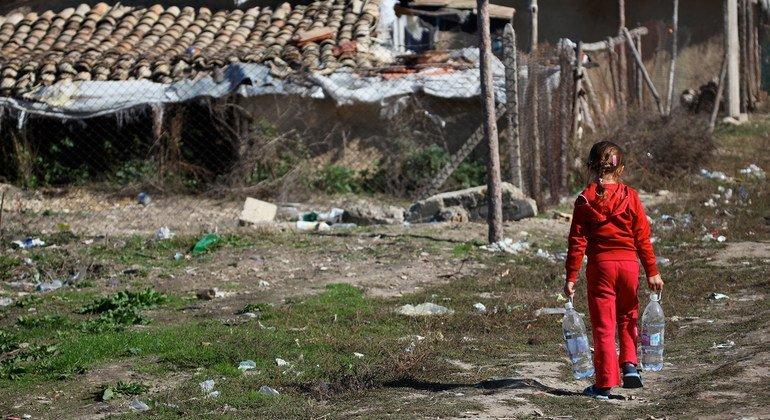 طفلة تحمل قوارير مياه وتسير باتجاه مجتمعها الفقير في شمال بلغاريا.