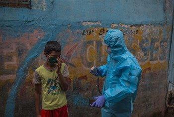 Un agent de santé sensibilise à la Covid-19 dans un bidonville de Mumbai en Inde.