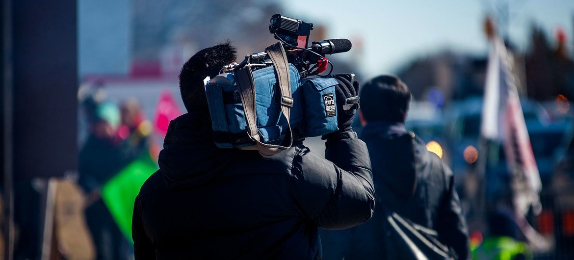 A video journalist covers a news event.