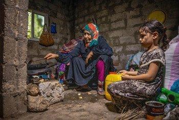 سيّدة مسنة وحفيدتها (6 سنوات) تجهزان الطعام في منزلهما في اليمن.
