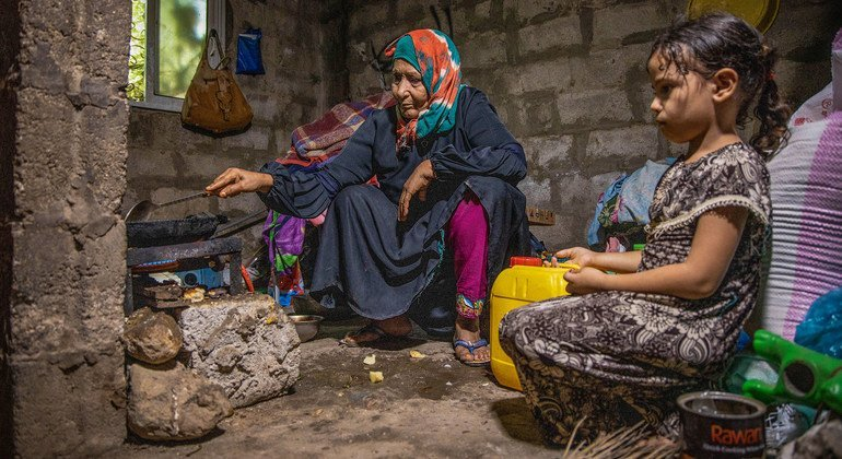 An elderly woman and her six-year-old granddaughter prepare lunch at home in Yemen.