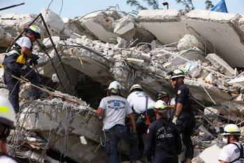 2010年1月12日海地地震后,救援人员在倒塌了联合国维和特派团总部大楼开展搜救工作。