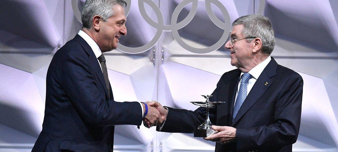 国际奥委会主席巴赫向难民署负责人格兰迪颁发奥林匹克奖杯。