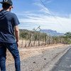 A young internally displaced man stands by the road on the outskirts of San Salvador in El Salvador.
