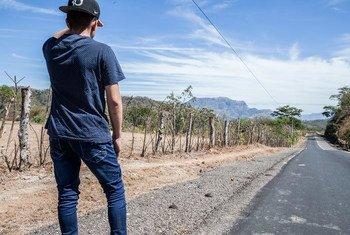Un jeune homme déplacé se tient au bord d'une route d'El Salvador.