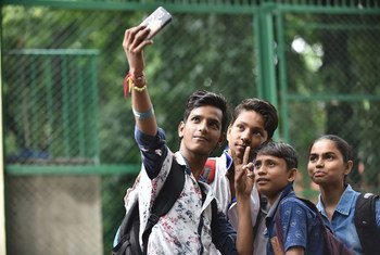 A boy uses his mobile phone to take a selfie with his friends at a school in New Delhi, India.
