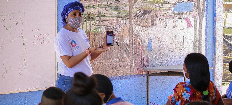 Una maestra explica cómo usar la aplicación para acceder al material educativo en los dispositivos móviles. La Guajira, Colombia