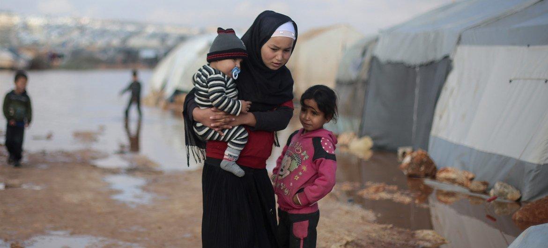 Unos niños están fuera de su tienda de campaña tras las inundaciones sufridas en enero de 2019 en el campamento de Kafr Losin, en el noroeste de Siria.