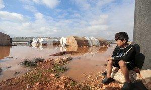 2021年1月19日,叙利亚西北部伊德利卜,一名流离失所的男童望着遭洪水淹没的营地。
