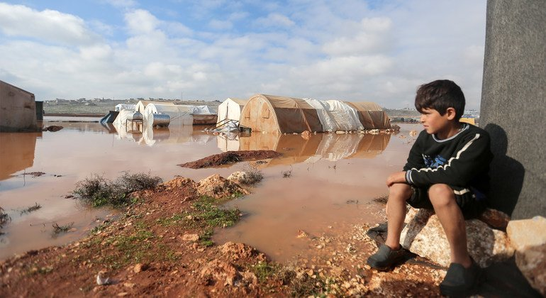 في 19 كانون الثاني/يناير، طفل ينظر إلى مخيم كفر لوسين في شمال غرب سوريا الذي تعرّض لفيضانات.