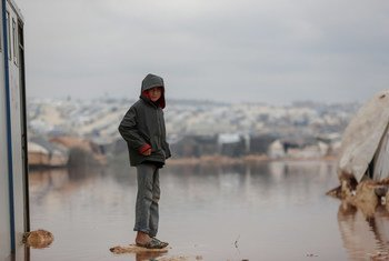 A child is surrounded by floodwater in Kafr Losin Camp in northwestern Syrian.