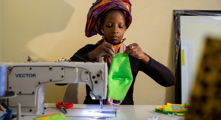 A woman sews face masks to sell during the COVID-19 crisis in South Africa.