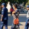 ज़िम्बाब्वे की राजधानी हरारे में कोविड-19 से बचाव के लिए मास्क पहने हुए एक महिला पुलिस अधिकारियों के पास से गुज़रते हुए. सभी को ऐहतियात बरतने को कहा गया है.