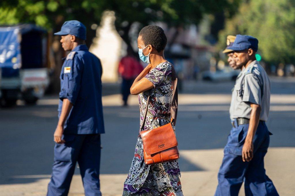 A Harare, au Zimbabwe, une femme portant un masque de protection contre la Covid-19 passe devant un groupe de policiers en patrouille à Bulawayo, le 1er avril 2020.