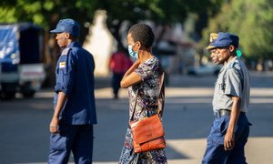 A woman wearing a COVID-19 protective mask walks past a group of police officers on patrol in Harare, Zimbabwe.