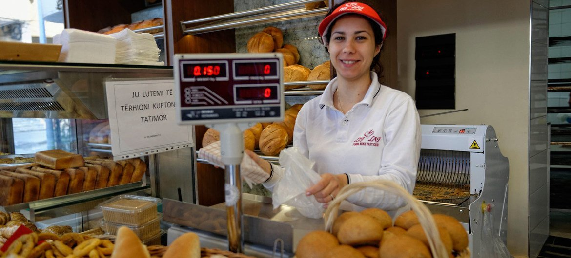 A shop worker sells bread in a bakery in Tirana, Albania