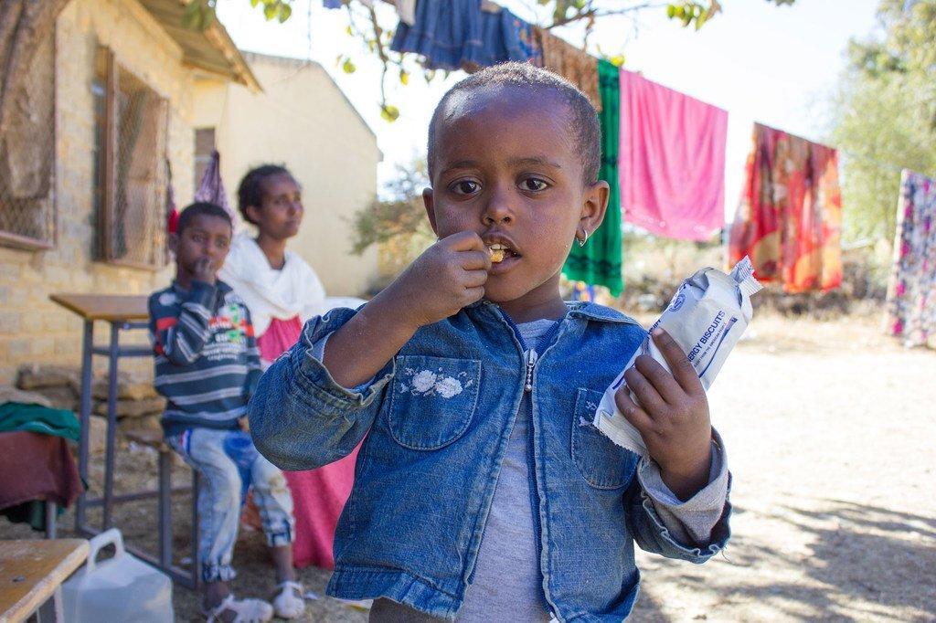 Msichana wa umri wa miaka 3 Magharibi wa Tigray akila biskuti za kuongeza nguvu kuinua kiwango cha lishe yake