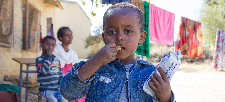 Une fillette de trois ans mange des biscuits à haute valeur énergétique dans la partie occidentale du Tigré.