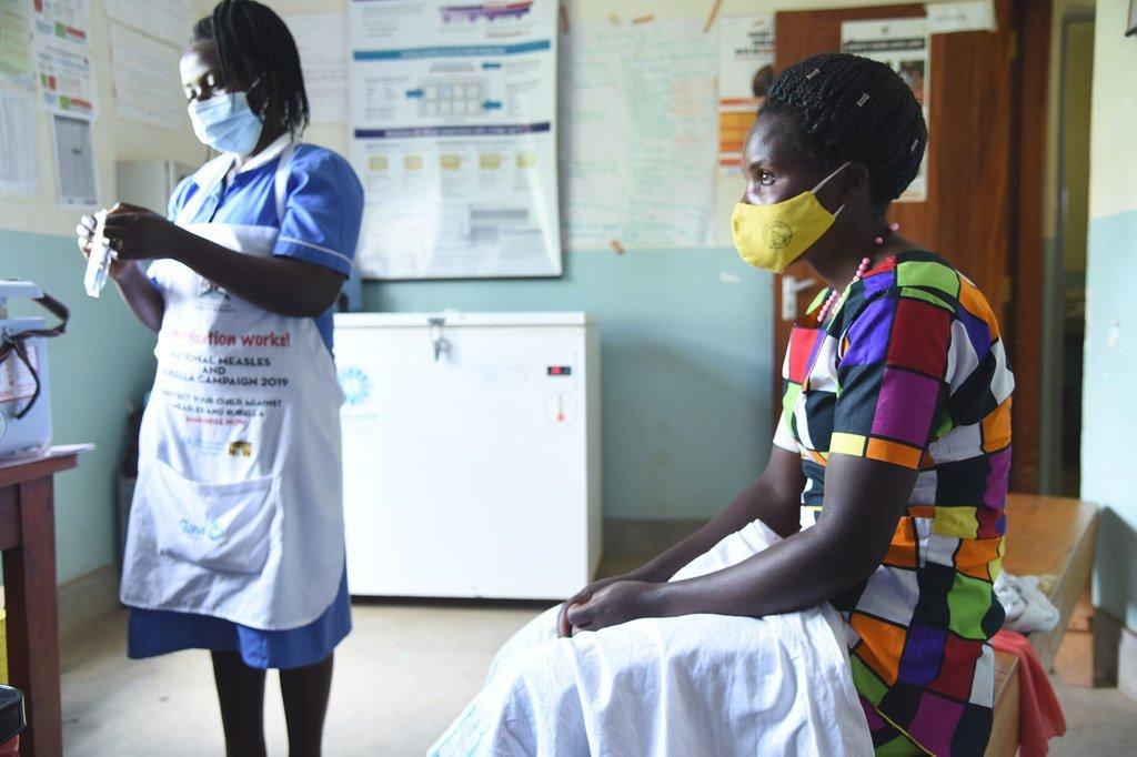 Une infirmière se prépare à administrer un vaccin contre la Covid-19 à une patiente dans un centre de santé à Kabale, en Ouganda.