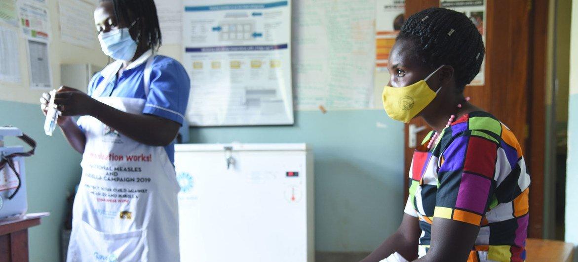 ممرضة تستعد لإعطاء لقاح كوفيد-19 لامرأة مركز صحي في كابالي بأوغندا.