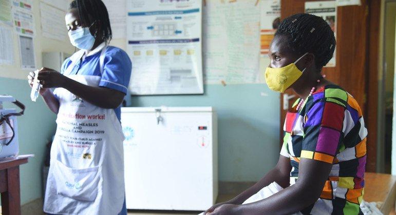Una enfermera se prepara para administrar una vacuna del COVID-19 a un paciente en un centro de salud de Kabale en Uganda