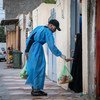 أحد المتطوعين يقدم الطعام لطفلة في كربلاء بالعراق بعد فرض حظر التجول بسبب فيروس كورونا.