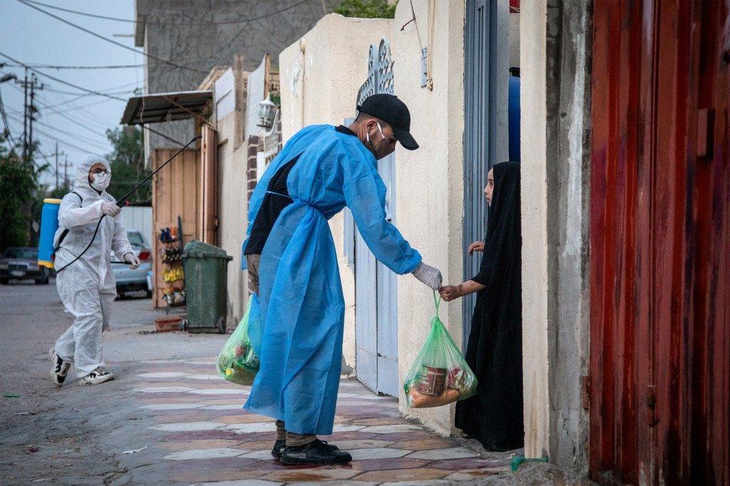 伊拉克中部城市卡尔巴拉,疫情封锁期间,一名志愿者向当地家庭分发食品。