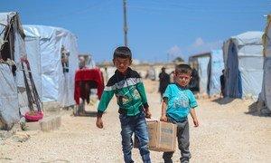 Irmãos Ahmad, de 7 anos, e Saad, de 5, cacarregam ajuda no assentamento de Fafin, em Alepo