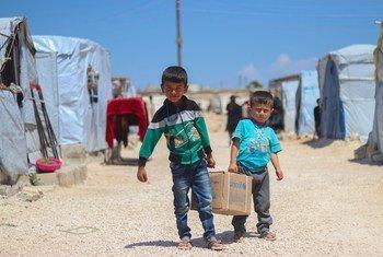 الشقيقان أحمد (يسار)، 7 أعوام، وسعد، 5، يحملان صندوقا فيه أدوات صحية ويسيران باتجاه خيمتهما في مخيم فافين في شمال حلب.