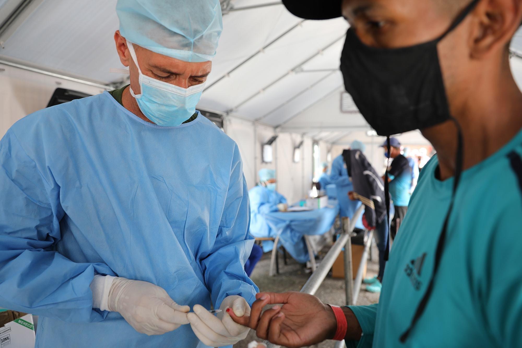 Los trabajadores de salud hacen la prueba rápida de COVID-19 a los venezolanos que regresan de Colombia a su país por el puente interancional Simón Bolívar.
