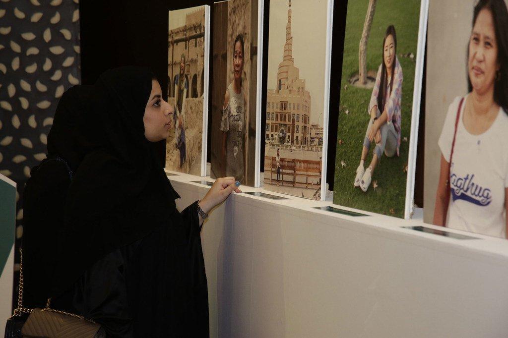 在国际家政工人日,卡塔尔一名妇女在休假时观看家政工人肖像展览。