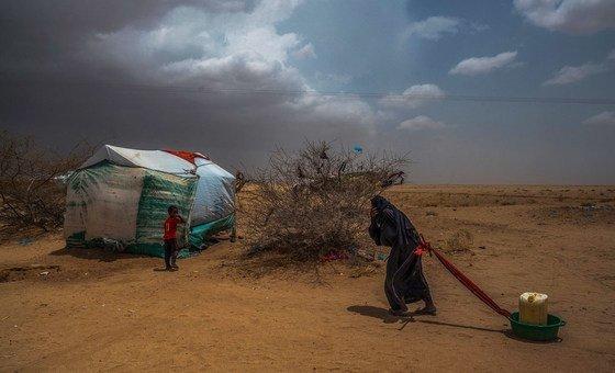 Idosa leva água para sua tenda em um campo de deslocados no norte do Iêmen, perto da fronteira com a Arábia Saudita