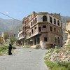 A woman walks in Taiz, a war-ravaged city in Yemen, split by a frontline.