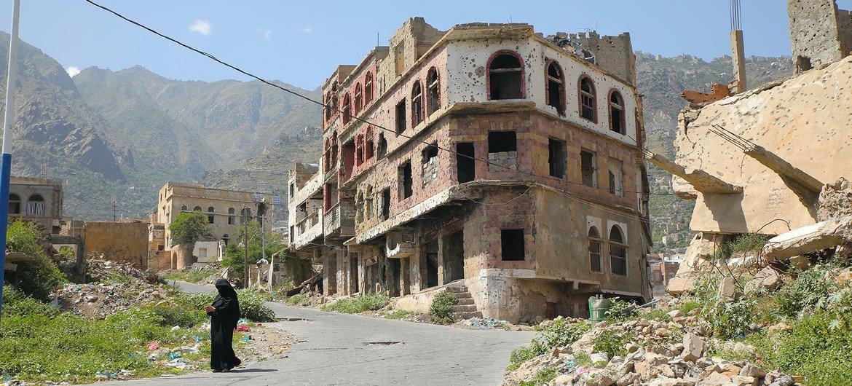 A pistillate   walks successful  Taiz, a war-ravaged metropolis  successful  Yemen, divided  by a frontline.